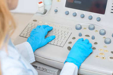 cropped shot of female obstetrician gynecologist in gloves working with ultrasonic scanner