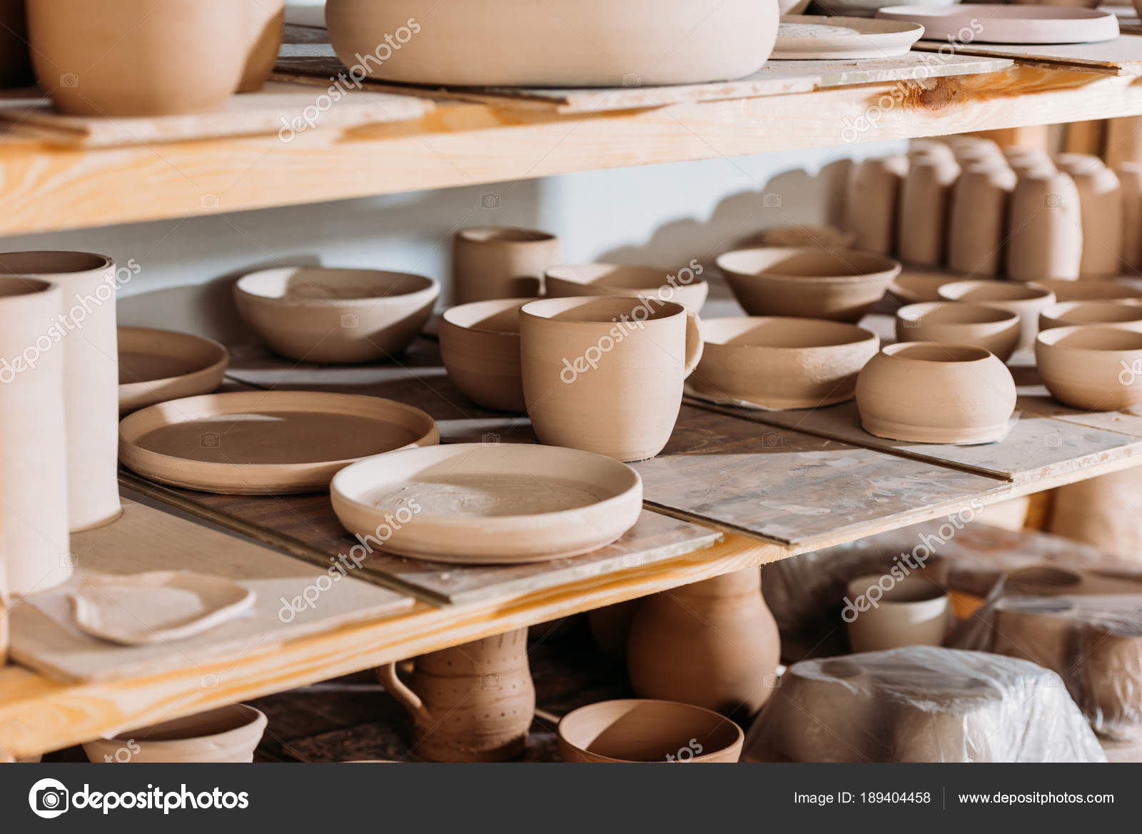 Ceramic plates and bowls on wooden shelves in pottery workshop u2014 Photo by IgorVetushko & Ceramic Plates Bowls Wooden Shelves Pottery Workshop u2014 Stock Photo ...