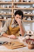 Müder Töpfer in Schürze sitzt mit Keramik in Werkstatt am Tisch