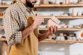Fotografia ritagliate la vista di stoviglie in ceramica di maschio potter pittura con pennello in officina