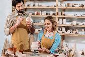 Fotografia felice ceramisti stoviglie in ceramica nel laboratorio di pittura
