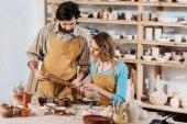 Fotografia paio di ceramisti con documenti, ceramica, vernici e pennelli in officina