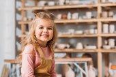 Fotografia bambino sorridente biondo che guarda lobbiettivo nel laboratorio di ceramica