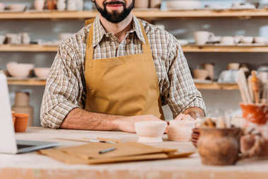 cropped view of man in apron in pottery workshop