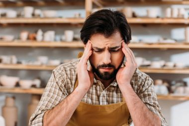 tired male potter having headache while sitting in workshop