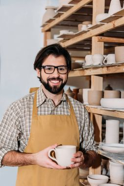 Smiling male potter holding cup and standing at shelves with ceramic dishware stock vector