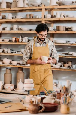 male potter with ceramic dishware in workshop
