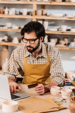 bearded man shopping online with laptop and credit card in pottery workshop