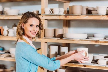 beautiful smiling potter with ceramic dishware on shelves in workshop