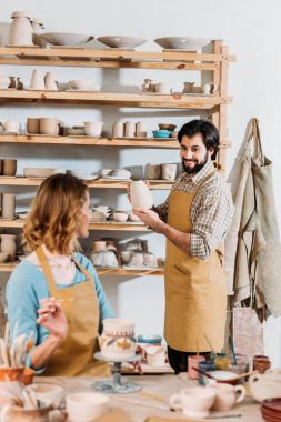 two potters working with ceramic dishware in workshop