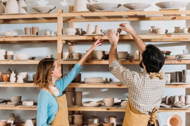 two potters with ceramic dishware in workshop