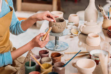 cropped view of female potter decorating ceramic bowl in workshop