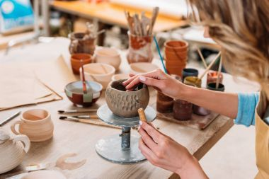 cropped view of woman decorating ceramic bowl in pottery workshop