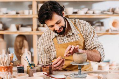 happy potter in apron decorating ceramic bowl in workshop
