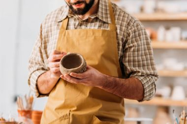 cropped view of man decorating ceramic bowl in pottery workshop