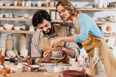 Couple of potters making ceramic dishware together in workshop stock vector
