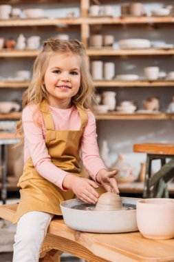 blonde smiling child learning to use pottery wheel in workshop