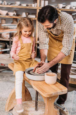 father teaching his daughter to use pottery wheel in workshop