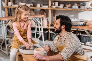 happy kid making ceramic pot on pottery wheel with teacher in workshop