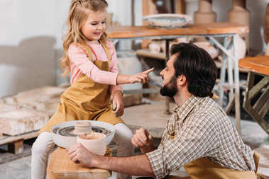 adorable daughter touching nose of father in pottery workshop