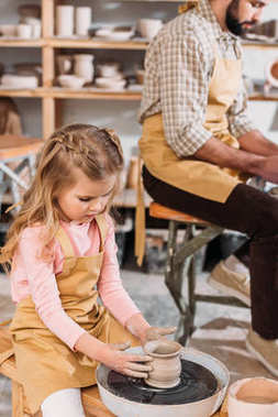 child making ceramic pot on pottery wheel with teacher in workshop