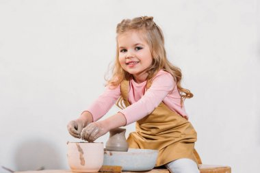 blonde smiling child making ceramic pot on pottery wheel in workshop