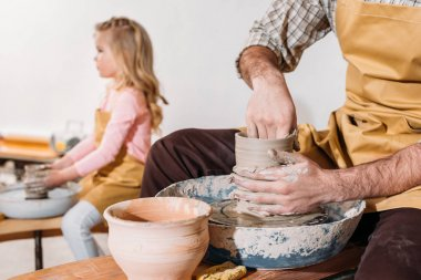 selective focus of daughter making ceramic pot on pottery wheel with father on foreground