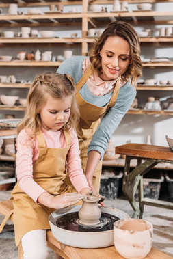 teacher and kid making ceramic pot in pottery workshop