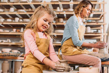 woman and kid making ceramic pots on pottery wheels in workshop