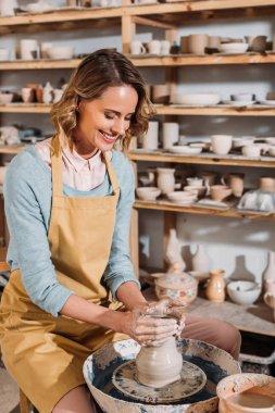 smiling female potter making ceramic pot on pottery wheel in workshop