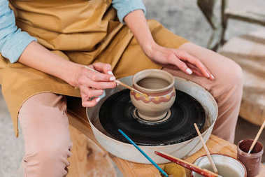 cropped view of woman painting traditional ceramic pot in pottery workshop
