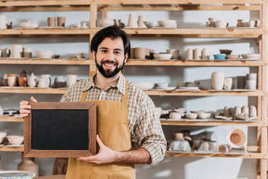 male bearded owner with chalkboard in pottery workshop with ceramics