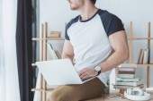 oříznutý pohled na mužské studenta s notebookem sedět na stole se sluchátky