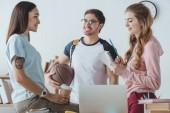 Fotografia giovani studenti seduti con il basket, caffè per andare e parlare insieme copybook