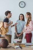 Fotografie mladí šťastní studenti stojí a mluví spolu