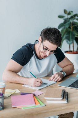 handsome smiling student in eyeglasses writing in copybook