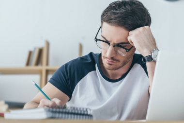 handsome male student in eyeglasses writing in copybook