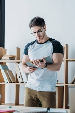 handsome student in glasses standing and reading book