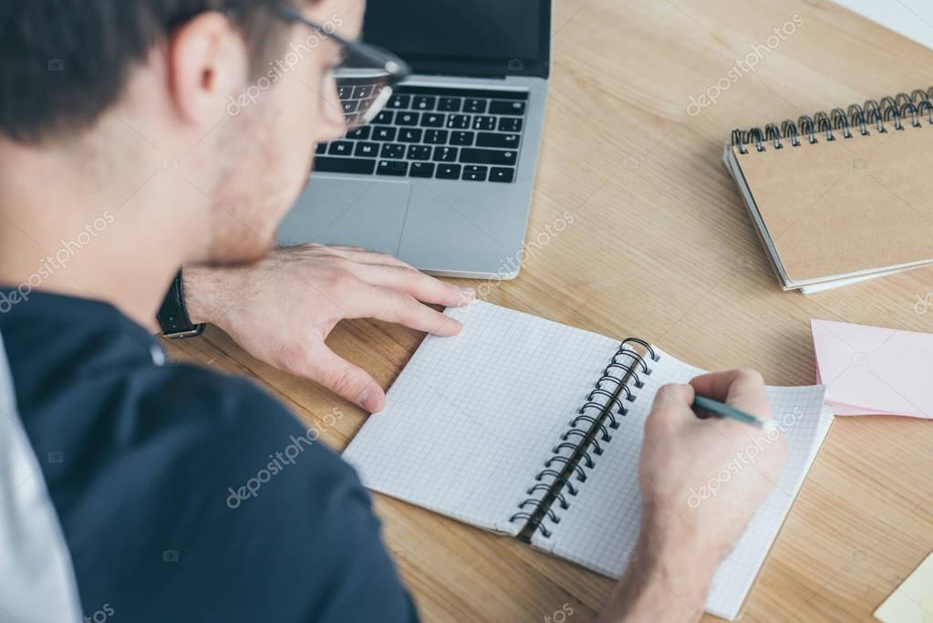 Selective focus of male student writing in copybook