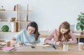 Fotografie multiethnische Studentinnen Prüfung gemeinsam schreiben