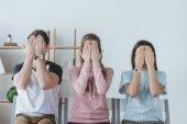mladí studenti zavírání obličeje s rukama