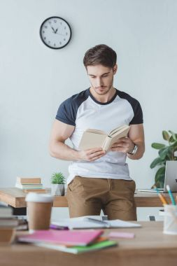 male student studying with book in room with copybooks