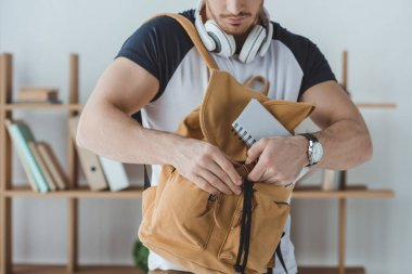 cropped view of student with headphones, backpack and notebook