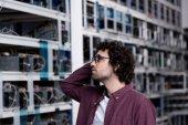 Nachdenklicher junger Computeringenieur betrachtet Kryptowährungs-Mining-Farm
