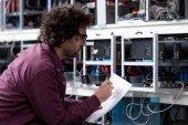 Junger Computeringenieur schreibt auf Kryptowährungsfarm auf Papier
