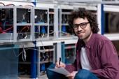 Junger lächelnder Computeringenieur sitzt auf dem Boden und schreibt auf Kryptowährungsfarm