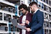 Fotografie podnikatel a počítače inženýr pracující s přenosným počítačem spolu v bitcoin těžby farm