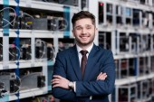 Photo smiling young businessman with crossed arms at cryptocurrency mining farm