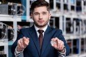 schöner junger Geschäftsmann mit Bitcoins auf Kryptowährungs-Mining-Farm
