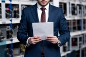 Photo cropped shot of young businessman with paperwork at cryptocurrency mining farm